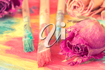 Abstract painting with dry roses and paint brushes