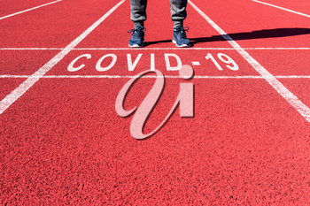 Win against virus. Athlete at the sprint start line in track with text COVID-19