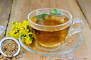 Tea in a glass cup, a metal filter for tea with dried flowers tutsan, Hypericum fresh flowers on the background of wooden boards