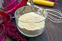 Amaranth flour in a glass cup, mixer, rolling pin, sieve and purple amaranth flower on the background of wooden boards