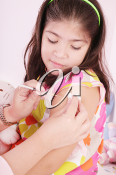 child receiving an injection by the hands of a pediatrician