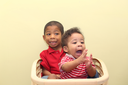 Two brothers of mixed race.  Focus in the front baby.