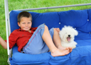 A blond smiling boy and a yawning puppy relaxing on a porch swing
