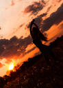 Silhouette of a dancing young girl against the sunset sky