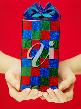 christmas gift in hands isolated on red