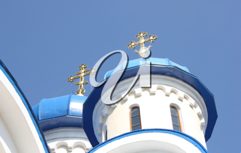 Dark blue church domes against the blue sky and gold crosses nearby