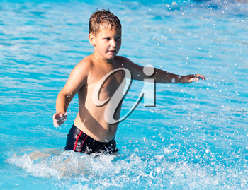 boy swims with a splash in the water park