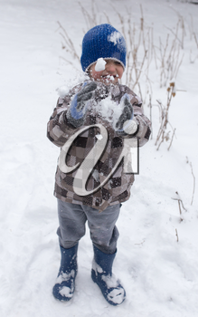 Boy playing with snow in winter