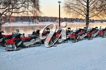 Vehicles are a number of snowmobiles in the parking lot