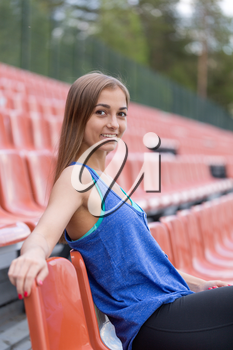 Portrait of a smiling brunette girl at the stadium.