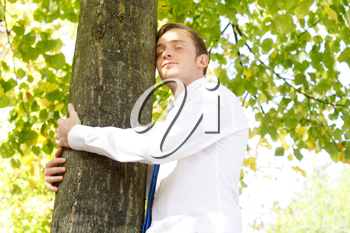 Royalty Free Photo of a Man Hugging a Tree