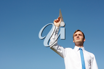 Royalty Free Photo of a Businessman Throwing a Paper Airplane