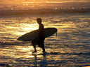 Royalty Free Photo of a Surfer Carrying His Board