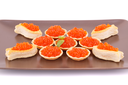 Red caviar in round pastries on brown plate.