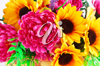 Colorful fabric flowers in wicker basket closeup picture.
