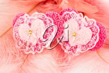 Two pink hearts with lace on feathers background.