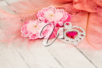 Two pink hearts with lace, jewelry with stone and feathers on gray wooden background.