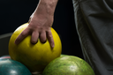 Holding Ball Against Bowling Alley