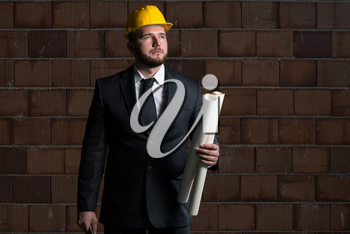 Portrait Of Construction Master With Yellow Helmet And Blueprint In Hands
