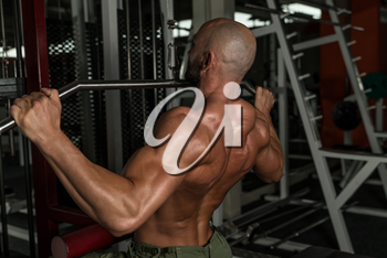 Mature Man Doing Back Exercises In The Gym