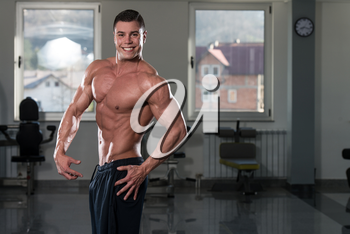 Portrait Of A Physically Fit Man Showing His Well Trained Body In Gym