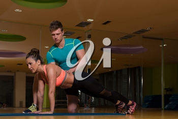 Personal Trainer Showing Young Woman How To Train Push-ups In The Gym