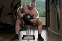 Muscular Man Doing Heavy Weight Exercise For Biceps With Dumbbells In Gym