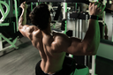 Young Bodybuilder Doing Heavy Weight Exercise For Back On Machine