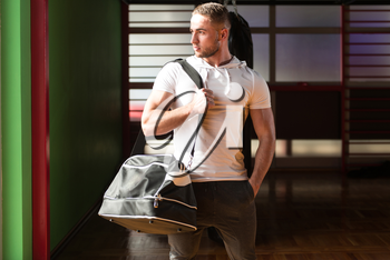 Fit young man with gym bag going on the in gym