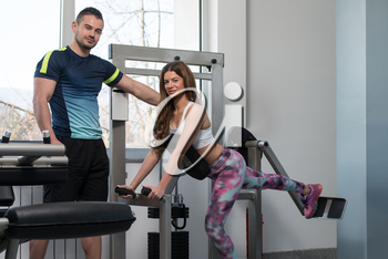Personal Trainer Showing Young Woman How To Train Legs On Machine In The Gym