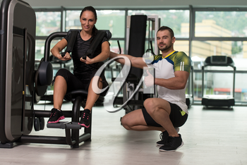 Personal Trainer Showing Ok Sign To Client - Man  Showing Young Woman How To Train Abs On Machine In The Gym