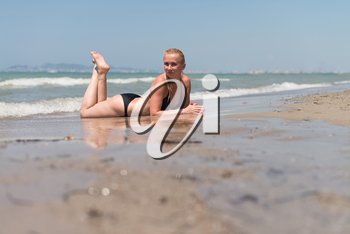 Young Beautiful Wet Blonde Woman Lying on the Beach Sand Near Ocean