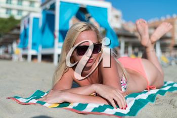 Beautiful Young Girl in a Pink Swimsuit and Sunglasses Is Lying on the Beach