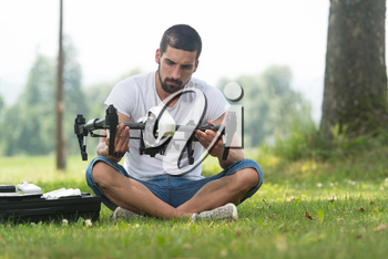 Young Engineer Man Prepares a Drone to Flight in Park