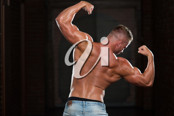 Portrait Of A Young Physically Fit Man In Jeans Showing His Well Trained Body - Muscular Athletic Bodybuilder Fitness Model Posing After Exercises