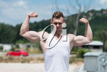 Healthy Young Man Standing Strong Outdoors  And Flexing Muscles - Muscular Athletic Bodybuilder Fitness Model Posing After Exercises
