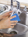Vertical photo of female hands cleaning a drinking glass with soapy water and a sponge with kitchen sink in background