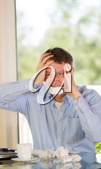 Vertical image of mature man showing stress by biting wad of paper while working from home with bright daylight coming in from window in background