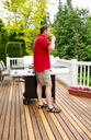 Closeup vertical photo of mature man drinking beer while looking at woods with BBQ grill and open cedar patio with seasonal trees in full bloom in background