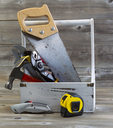 Vertical view of an old tool holder containing basic home repair tools on rustic wooden boards