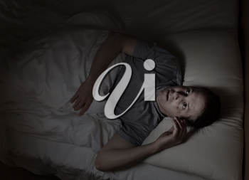 Top view image of mature man restless in bed from insomnia