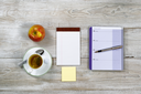 Top view of business office objects with food and drink on rustic white wooden desktop