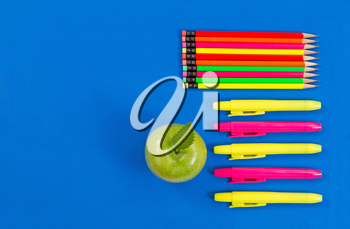 Office or back to school supplies consisting of a green apple, highlight markers and colorful pencils on blue background.