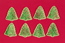 Christmas tree shaped cookies organized on red background.