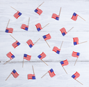 Small USA flags scattered on rustic white wooden boards. Fourth of July holiday concept for United States of America.