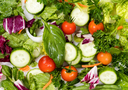 Overhead view of a fresh salad consisting of cherry tomatoes, parsley, basil, onion, cucumber, and green beans. Filled frame format.