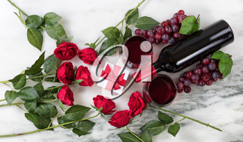 Overhead view of Red wine bottle, glasses, grapes and roses on natural marble stone setting