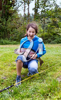 Teen girl holding large trout with big smile