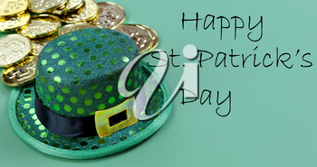 Close up of a St Patricks day Irish elf hat and shiny gold coins in background on green setting with copy space plus text message