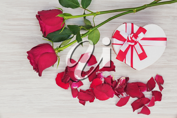 Valentine`s Day gift and roses on wooden background. Closeup.